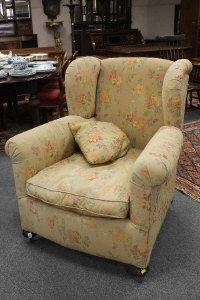 A Victorian style wingback armchair upholstered in a floral fabric, width 92cm.