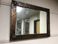 An Arts and Crafts copper framed mirror, width 59 cm.