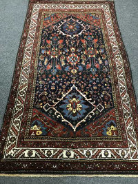 A Persian rug, with a central blue medallion of stylized flowers, enclosed by cream borders, 254 cm x 142 cm.