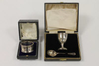 A silver egg cup and spoon, together with a silver napkin ring, both parts cased. (2)
