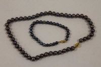 A Tahitian black pearl necklace with 9ct gold clasp, together with a similar bracelet. (2)