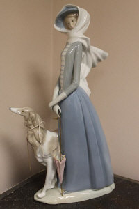 A Lladro figure - A Lady walking a dog in a strong breeze, height 40 cm.