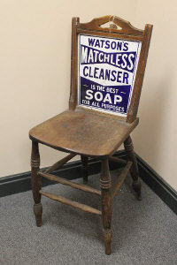 An early twentieth century kitchen chair with enamelled advertising panelled back 'Watson's Matchless Cleanser'.