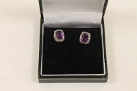 A pair of 9ct gold diamond and amethyst stud earrings. (2)