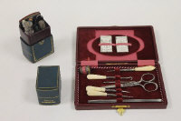 A Lady's companion, contained within a leather 'book', together with  a sewing set, cased. (2)