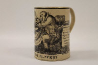 A rare late eighteenth century Newcastle Pottery creamware frog mug, decorated with political satire of 'British Slavery', the cartoon showing a man eating and exclaiming against taxes making '... Slaves of us all..', height 12.5 cm.