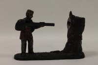 A late nineteenth century American cast iron Creedmoor bank depicting a man shooting a rifle into a tree, height 17 cm.