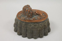 A Victorian copper jelly mould surmounted by a recumbent lion .