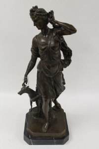 After Moreau - A bronze figure depicting a lady with dog, on black marble plinth, height 63 cm.