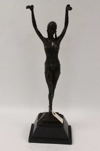 After Demetre H. Chiparus - A bronze figure depicting an Art Deco style lady with her arms raised, on marble plinth, height 62 cm.