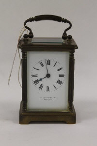 A brass French carriage clock, retailed by Sharman D.Neill, Belfast.