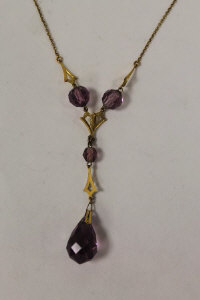 A 9ct gold necklace with amethyst drop pendant.