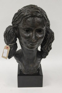 A bronze study of a young girl with pigtails, on black marble plinth, height 45 cm.