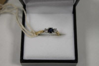 An 18ct gold three stone diamond and sapphire ring.