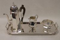 A three piece silver coffee service, London 1982, 38 oz, standing upon a silver-plated oblong tray on ball feet. (4)