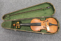 An early twentieth century violin and bow in coffin case, back length 36 cm.