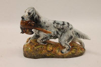 A Royal Doulton figure : English setter with pheasant, model 1028, grey with black markings, red/brown cock pheasant, yellow/brown leaves on base, height 22 cm.