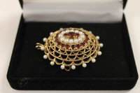 A 9ct gold seed pearl and garnet brooch.