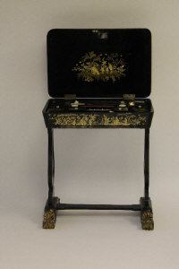 A nineteenth century lacquered work table, the compartmentalised interior containing ivory accessories, width 62 cm.