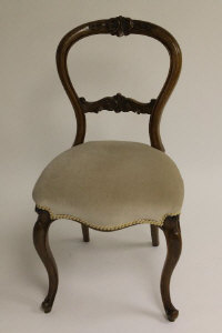 A set of six Victorian walnut balloon backed chairs. (6)