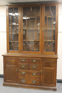 An Edwardian oak bookcase, fitted with four drawers, width 153 cm.