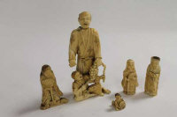 A nineteenth century Japanese ivory figure depicting two men clutching a vine, together with four miniature ivory figures of the same period. (5)