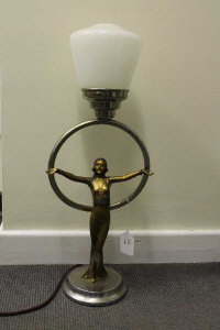 An Art Deco patinated spelter table lamp with glass shade, height 57.