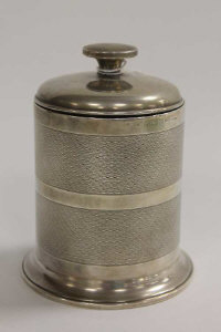 A silver cigarette dispenser with engine-turned sides, height 11.5 cm.