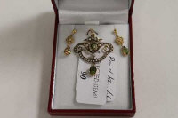 An Edwardian 9ct gold seed pearl and peridot pendant with matching earrings. (3)