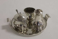 A silver three piece condiment set on silver tray. (4)