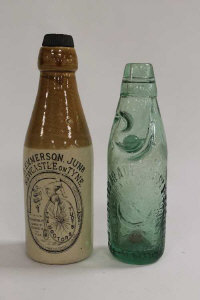 An advertising stoneware bottle by Buchan Edinburgh,  'R Emmerson, The Doctor's Stout Newcastle on Tyne', height 21 cm, together with a Licensed Trade Supply Society glass cod bottle. (2)