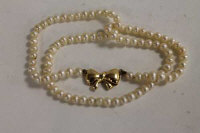A pearl necklace with 9ct gold bow clasp.