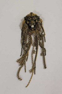 A Chanel goldtone costume Lion mask brooch, the jaw clutching a faux pearl.