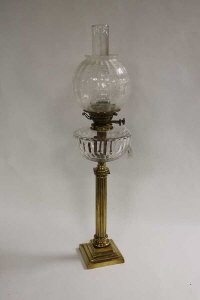 A nineteenth century brass oil lamp with glass reservoir and shade, height 78 cm.