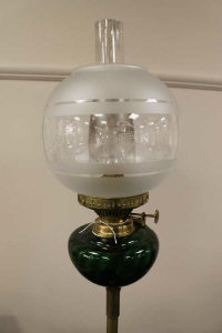 A late nineteenth century brass telescopic oil lamp with green glass reservoir.