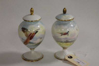 A pair of Minton hand painted miniature urns, decorated with pheasants in flight, signed by A. Holland, height 15.5 cm. (2)