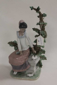 A Lladro figure - Lady seated  by a tree, height 32 cm.