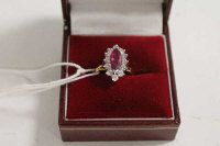 An 18ct gold marquise ruby and diamond cluster ring.