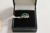 An 18ct gold three stone emerald and diamond ring.