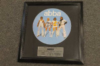 A limited edition Abba picture disc, together with a Marilyn Monroe photographic montage and James Bond 007 movie poster, all parts framed. (3)