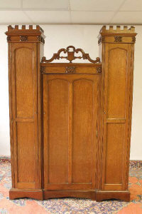 An Arts and Crafts oak cabinet with castellated frieze, width 133 cm.