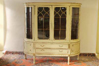 A cream and gilt display cabinet, fitted with two drawers and two cupboard doors, width 182 cm.
