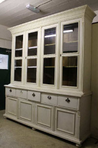 A painted white four door glazed kitchen cabinet, width 227 cm.