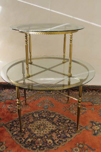 A pair of gilt metal and glass two tier display tables, height 132 cm. (2)