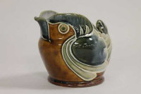 A Doulton Lambeth tubelined milk jug modelled as a small bird, height 11 cm.