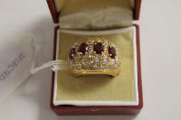 An 18ct gold four stone ruby and diamond encrusted ring.