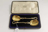 A pair of silver-gilt serving spoons, with engraved serpent stems, London 1901, cased.