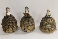 A set of three early twentieth century porcelain topped table lamps modelled as Ladies wearing shell dresses. (3)