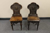 A pair of late Victorian carved oak hall chairs. (2)