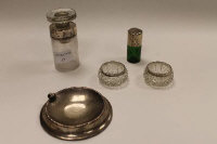 A green glass flask with silver top, together with a silver ashtray, a pair of silver rimmed salts and a glass bottle with silver collar. (5)